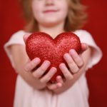A little girl stands with a heart in her hands  symbolizing the heart of children - Charity, love, compassion